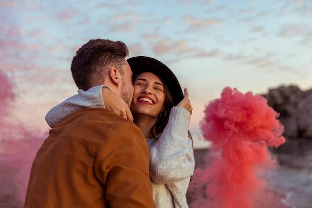 Man with smoke bomb kissing woman on cheek