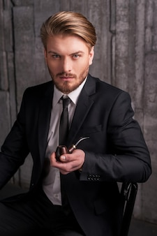 Man with a smoking pipe. handsome young man in formalwear holding a smoking pipe and looking at camera while sitting on the chair