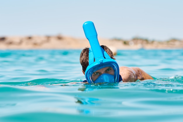Man with a snorkel full face mask diving in blue sea. summer vacation