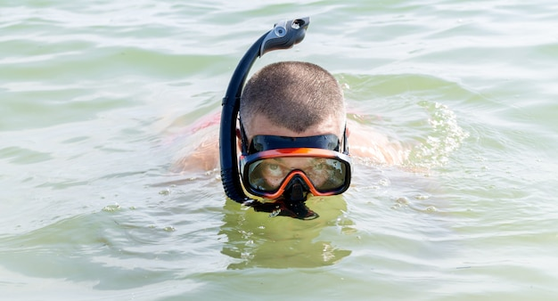 Man with snorkeling equipment: snorkel and scuba mask on the sea water