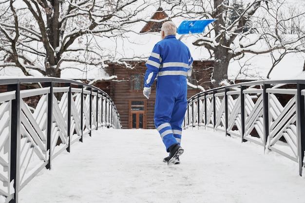 Человек с лопатой снег на плечо вид сзади.