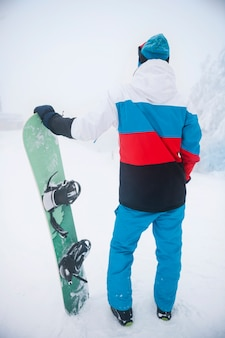 Man with snowboard during winter time
