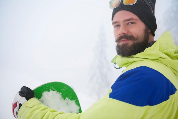 Uomo con lo snowboard durante il periodo invernale