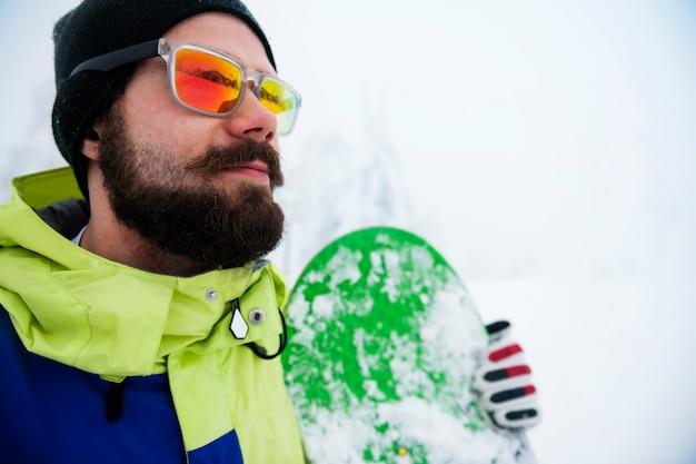 冬の間にスノーボードを持つ男
