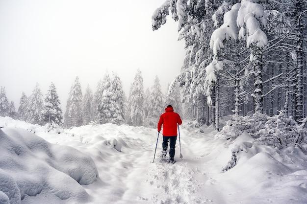 雪の中を歩くスノーシューと赤いジャケットを持つ男