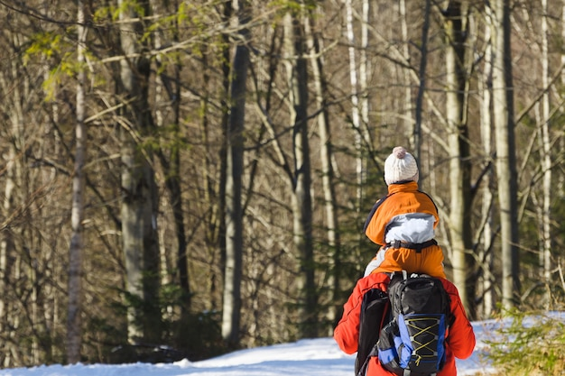 Man with son on shoulders walking along the road in a snowy forest.