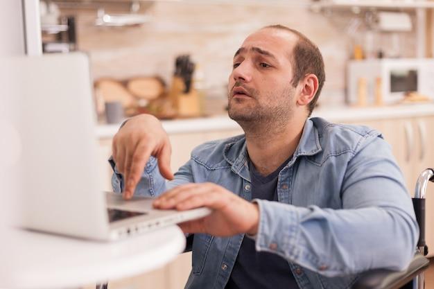 キッチンでラップトップに取り組んでいる車椅子の特別なニーズを持つ男。事故後に統合した歩行障害のある障害者麻痺障害者。