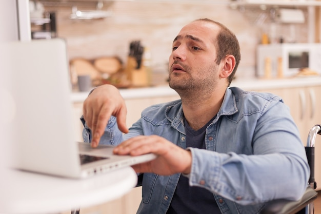 Man with special needs in wheelchair working on laptop in kitchen. disabled paralyzed handicapped man with walking disability integrating after an accident.