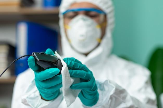 Человек в специальном белом костюме чистит компьютерную мышь