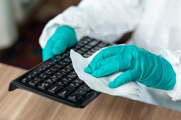 Человек в специальном белом костюме чистит клавиатуру компьютера