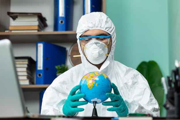 Человек в специальном белом люксе держит глобус земли рукой в офисе