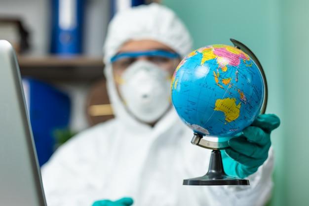 オフィスで片手で地球を保持している特別な白いスイートを持つ男