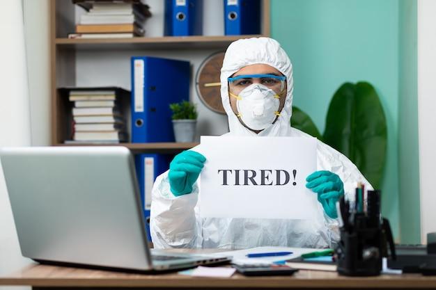 オフィスで疲れた言葉を保持している特別な白いスイートを持つ男