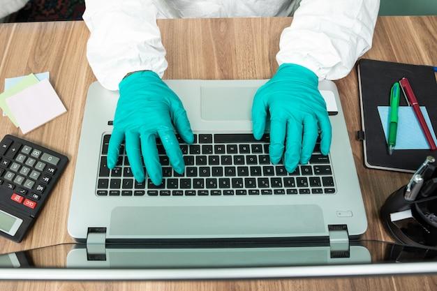 Человек со специальным белым набором работает на ноутбуке в офисе, вид сверху