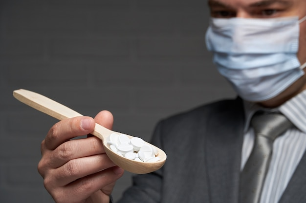 A man with spoon full of pills - healthcare and medicine concept, prevention tips