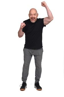 Человек в спортивной одежде с поднятым кулаком на белом фоне