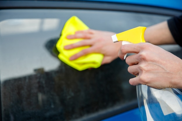 Man with a spray bottle and a rag in his hand wipes the dirty glass of a car