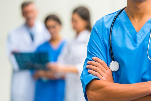 A man with a stethoscope is standing and folding his arms.