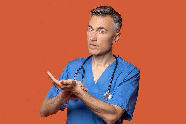 彼の脈拍を聞いている聴診器を持つ男
