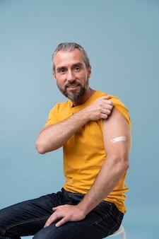 ワクチン接種後、腕にステッカーを貼った男