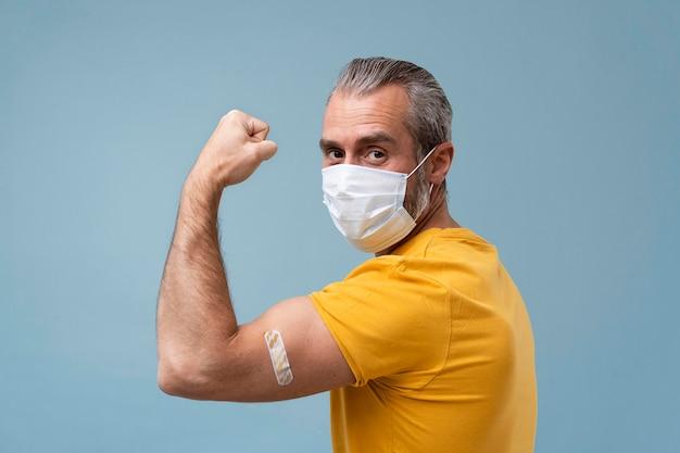 Человек с наклейкой на руке после вакцинации