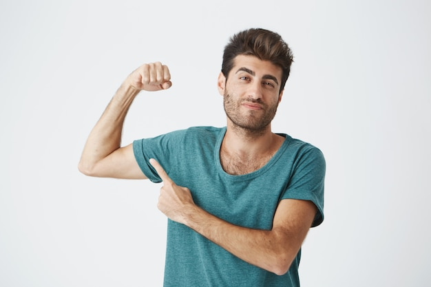 Man with stylish hairstyle and beard frowning his eyebrow, demonstrating how strong he is. fit guy pointing with his finger at his biceps. macho man showing himself