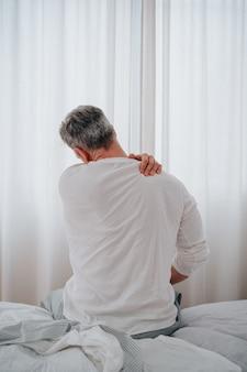 침대에서 목 통증으로 고통받는 50대 남성