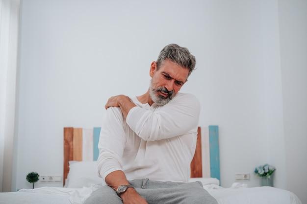 Мужчина 50 лет со страдающим лицом и болью в шее в постели