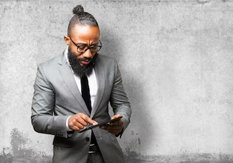 Man with suit touching the screen of a tablet