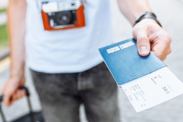 A man with a suitcase and a camera, holding a passport and tickets close-up