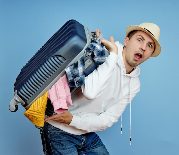Man with a suitcase hurries to the plane, things fall out of the luggage