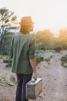 Man with suitcase in nature