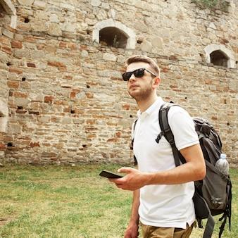城の遺跡でサングラスを持つ男
