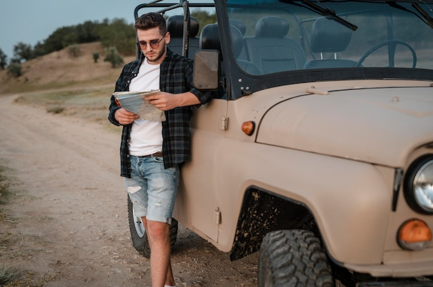 Man with sunglasses checking map while traveling by car