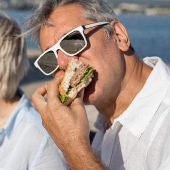 Человек в солнечных очках ест гамбургер на открытом воздухе