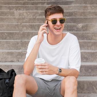 Человек в темных очках пьет кофе на открытом воздухе и разговаривает по телефону
