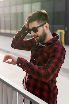 Man with sunglasses holding head and looking at watches