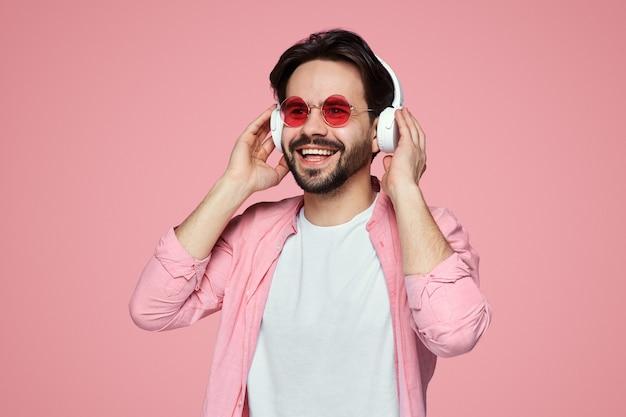 Человек в темных очках слушает музыку в наушниках над розовой стеной