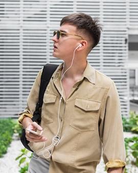 イヤホンで音楽を聴くサングラスを持つ男