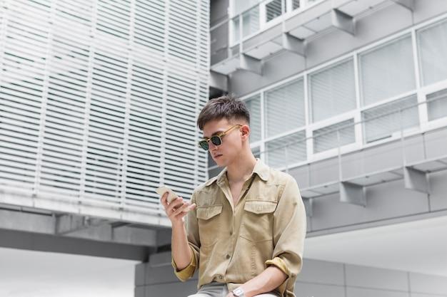 Человек в солнцезащитных очках, глядя на смартфон на открытом воздухе
