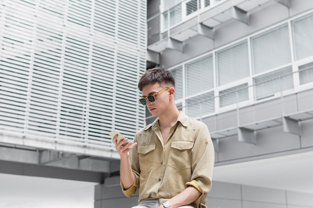 Man with sunglasses looking at smartphone outdoors
