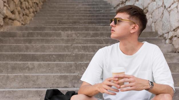 Человек в солнцезащитных очках сидит на ступеньках на открытом воздухе и пьет кофе