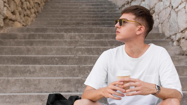 Man with sunglasses sitting on steps outdoors and having coffee