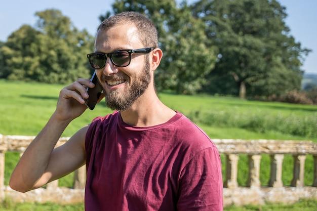 笑顔で携帯電話に話しているサングラスを持つ男