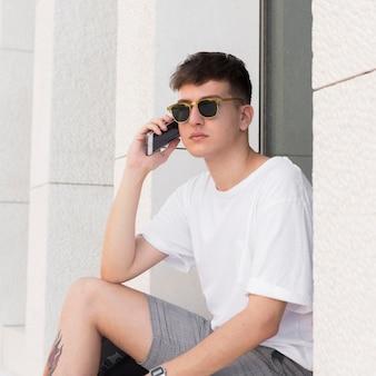 Человек в темных очках разговаривает по телефону на открытом воздухе