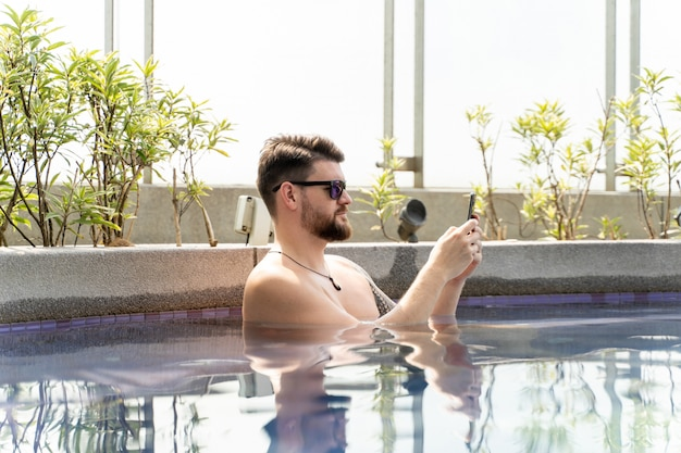 Man with sunglasses using his mobile in a pool
