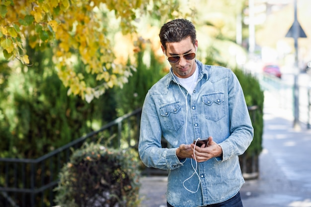 Man with sunglasses walking and looking at his mobile