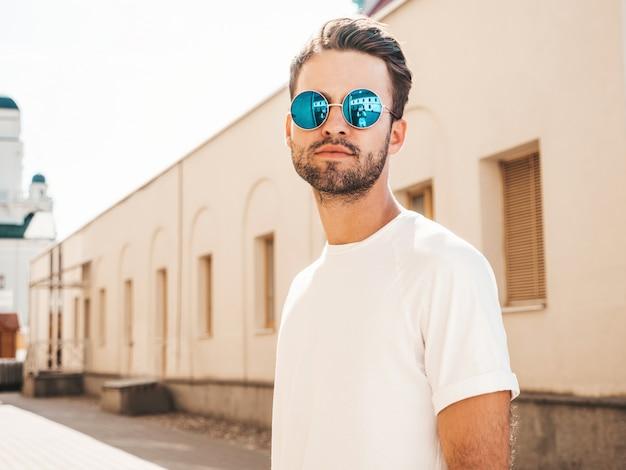 Uomo con gli occhiali da sole che indossano posa bianca della maglietta
