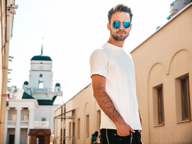 Человек в темных очках в белой футболке позирует