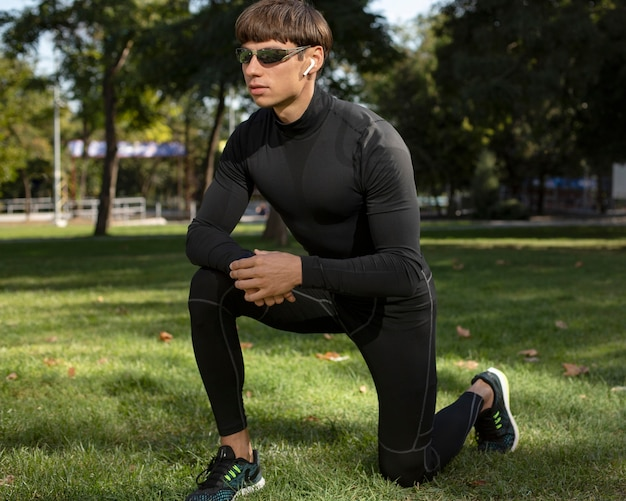 Man with sunglasses working out outdoors while wearing earbuds